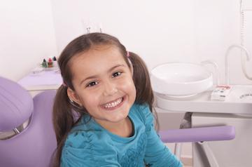 young girl sitting in dental exam chair smiling I pediatric dentistry at temple dental trails