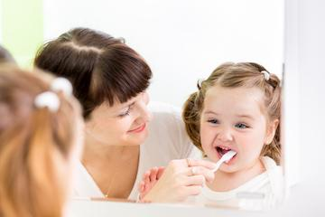 little girl with mother brushing teeth I childrens dentistry in temple tx