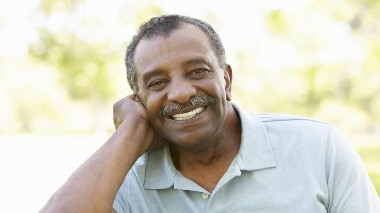 Older man smiling with hand on cheek l Dental Implants Temple TX
