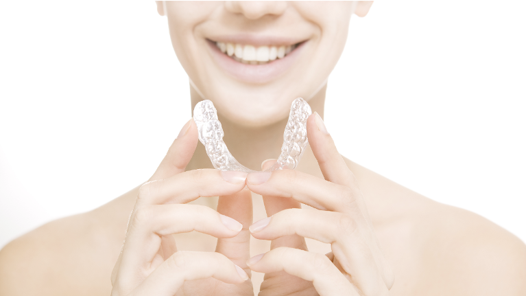 A Woman Holds Her Retainer | Temple TX Dentist