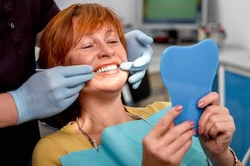 Woman sitting in dental exam chair smiling l dentist near me